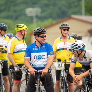 A group of 5 male cyclists wait at the start of the 2019 ride