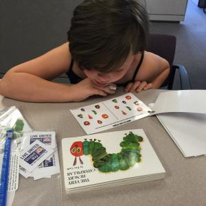 "Youngster plays learning game with book ""The Very Hungry Caterpillar."""